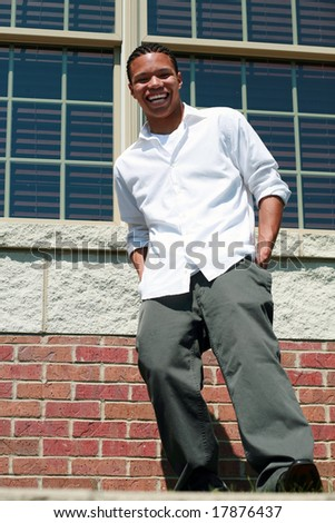full length of African-American teen boy smiling outside of school