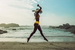 Full length of african woman in bikini running on the beach. Female model on the sea shore enjoying herself.
