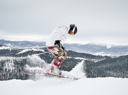 Full length of alpine skier skiing on fresh powder snow in winter mountains. Man freerider in winter ski pants making jump while sliding down snow-covered slopes. Concept of winter sports.