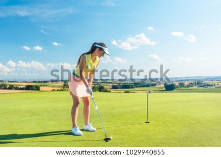 Full length of an attractive fit woman smiling while holding a putter golf club before hitting the ball during professional practice on putting green
