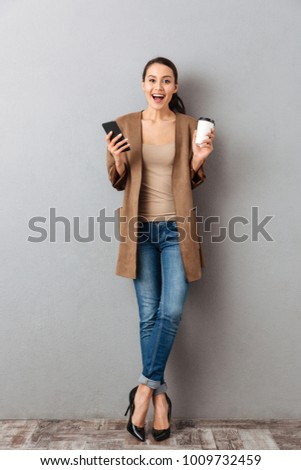 Full length of an excited young asian woman holding mobile phone while standing and holding cup of coffee over gray background