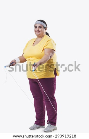 Full length of an overweight female with skipping rope over white background