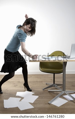 Full length of angry young businesswoman banging at desk