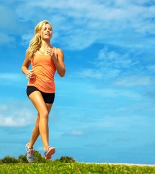 Full length of attractive young female athlete jogging on sidewalk at beach