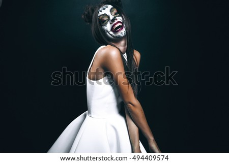 Full length of attractive young woman with gothic vampire makeup on helloween party over black background,halloween make up face