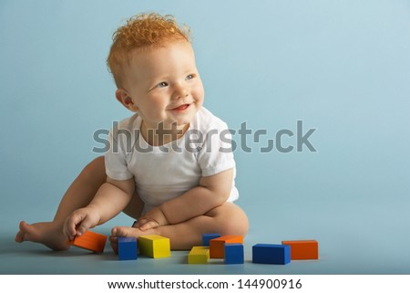 Full length of baby boy playing with building blocks isolated on blue background