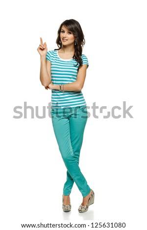 Full length of beautiful blond woman pointing up at copy space over white background