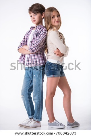 Full length of beautiful little girl and boy looking at camera and smiling while standing with crossed arms back to back on light background