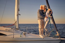 Full length of beautiful romantic senior couple standing on the side of sail boat or yacht deck floating in the calm blue sea, hugging and enjoying amazing sunset