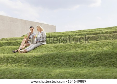 Full length of beautiful young businesswomen using laptop while sitting on grass steps against sky