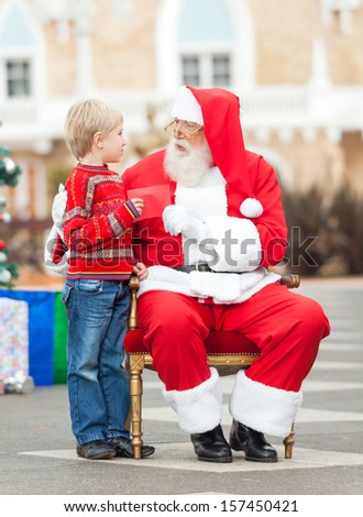 Full length of boy giving wish list to Santa Claus in courtyard