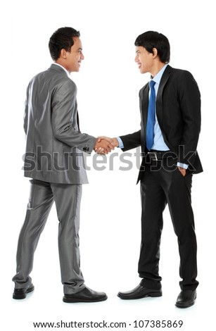 Full length of business colleagues shaking hands and smiling