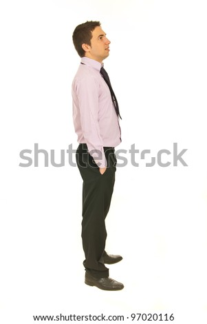 Full length of business man standing in profile with hands in pockets pants and looking away isolated onw hite background