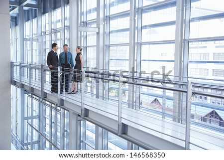 Full Length Of Business People Discussing By Railing In Modern Office