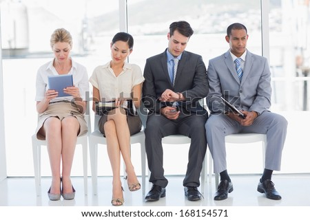 Full length of business people waiting for job interview in a bright office