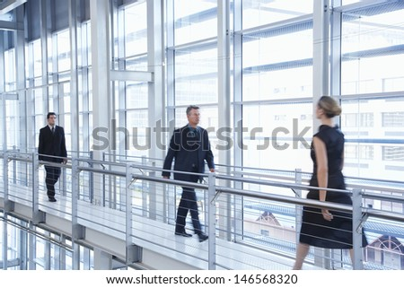 Full length of business people walking by railing in modern office