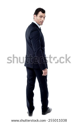 Full length of businessman looking over his shoulder
