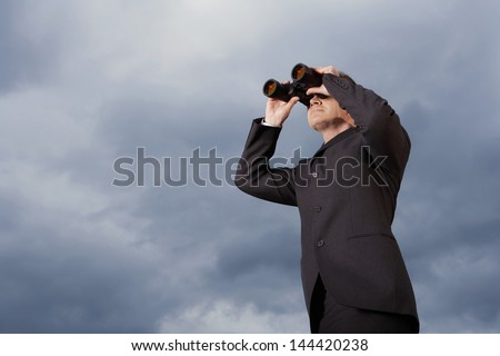 Full length of businessman looking through binoculars against cloudy sky