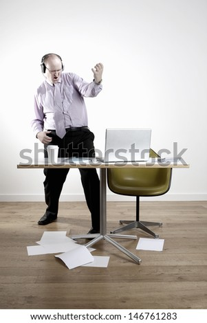 Full length of businessman wearing headphones while playing air guitar at office desk