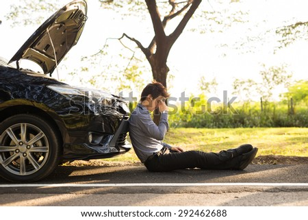 Full length of businessman with hands on head sitting by broken down car at countryside