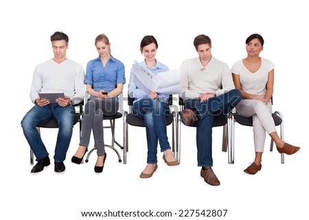 Full length of businesspeople doing various activities while sitting on chairs against white background #227542807