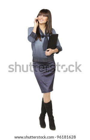 Full length of businesswoman standing with laptop talking on mobile phone, isolated on white background