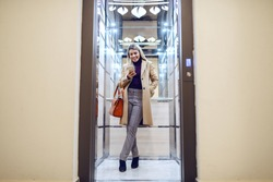 Full length of cheerful caucasian blonde woman in coat standing in elevator and using smart phone.