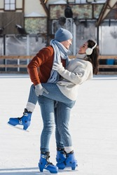 full length of cheerful man lifting leg of happy girlfriend on ice rink