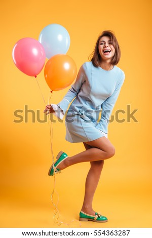 Full length of cheerful young woman with balloons standing and laughing #554363287