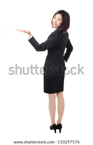 Full length of confident business woman showing something isolated over white background, view from back, model is a asian beauty