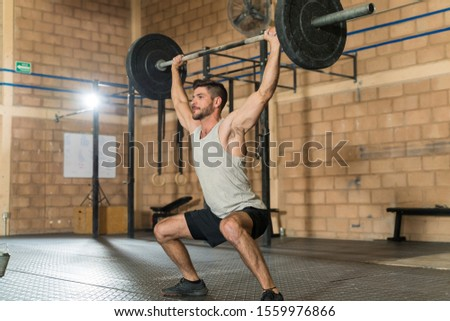 Full length of confident handsome sportsman holding barbell over his head while looking straight at health club