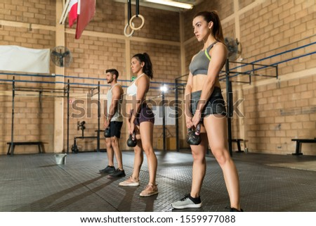 Full length of confident young male and female athletes holding kettlebells during cross training at health club