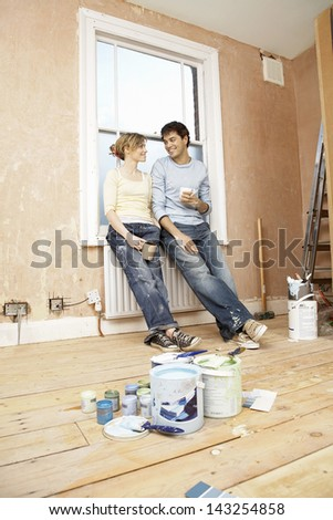 Full length of couple holding coffee mugs while looking at each other with paint cans in foreground