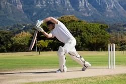 Full length of cricketer playing on field during sunny day