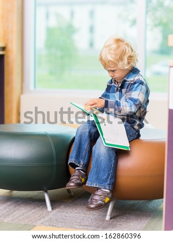 Full length of cute boy reading book on seat in school library