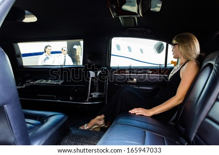 Full length of elegant woman in limousine at airport terminal