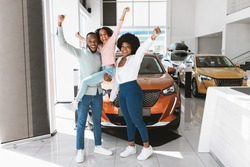 Full length of excited African American family lifting hands up, celebrating new car purchase at auto dealership. Black parents with daughter making YES gesture after buying vehicle at showroom