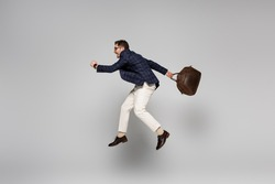 full length of excited businessman holding leather bag and levitating on grey