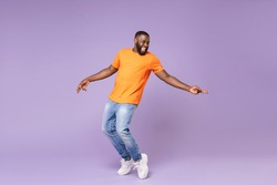 Full length of excited funny young african american man 20s in basic casual orange t-shirt dancing standing on toes pointing index fingers aside isolated on pastel violet background studio portrait