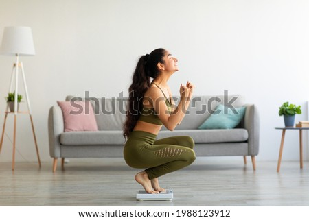 Full length of excited Indian woman sitting on scales at home, overjoyed with success of her slimming diet, side view. Emotional Asian lady achieving her weight loss goal, making YES gesture Photo stock ©