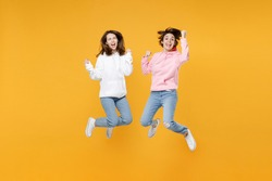 Full length of excited two young women friends 20s in basic white pink hoodies jumping doing winner gesture celebrating clenching fists say yes isolated on yellow color background studio portrait