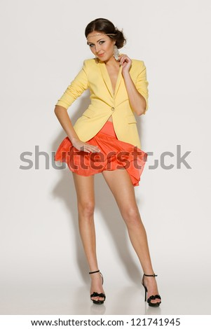 Full length of fashion model posing in mini skirt fluttering on the wind