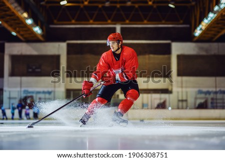 Full length of fearless hockey player skating towards goal and trying to make a score. Hall interior. Winter sports. Photo stock ©