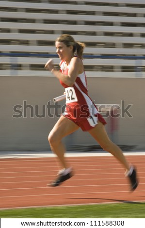 Full length of female athlete running with baton in race track