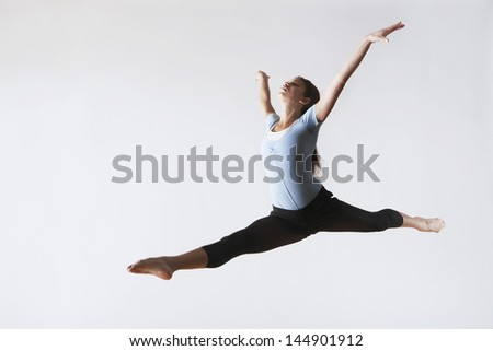 Full length of female ballet dancer leaping in mid air isolated on white background
