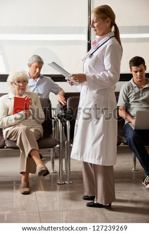 Full length of female doctor reading file with people sitting in hospital lobby