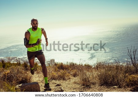 Full length of fitness man running over rocky trail on mountain. Fit young man running up a hill.