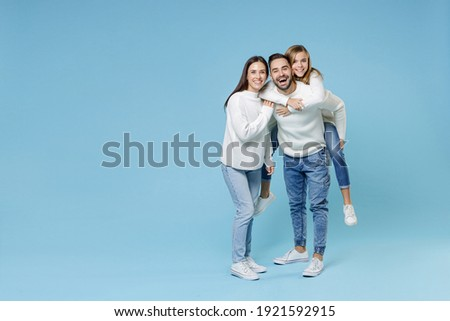 Full length of funny young parents mom dad with child kid daughter teen girl in sweaters giving piggyback ride to joyful, sitting on back isolated on blue background. Family day parenthood concept