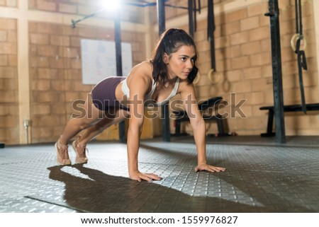 Full length of gorgeous young female athlete doing push-ups on floor at health club