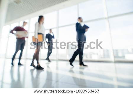 Full length of group of happy young business people walking the corridor in office together #1009953457